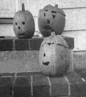 Three pumpkins on the stoop. Middle pumpkin with a frown
