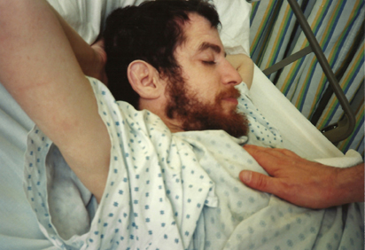 caressing brother mike in hospital bed