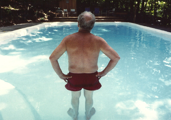Dad contemplating, looking out into a swimming pool