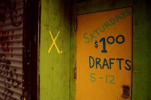 Photograph: Alternate View of Block Letter Graffiti on Side Door of X. Bar