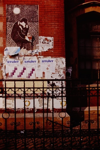 Photograph: Building Facade with Posters and Woodcut-Like Image