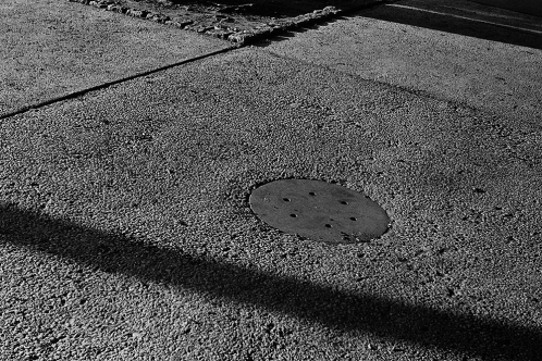 Photograph: Manhole Cover and Granular Sidewalk