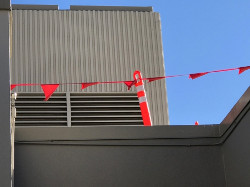 Photography: Street Photography - Red Barrier In Front of Vertical and Horizontal Stripes