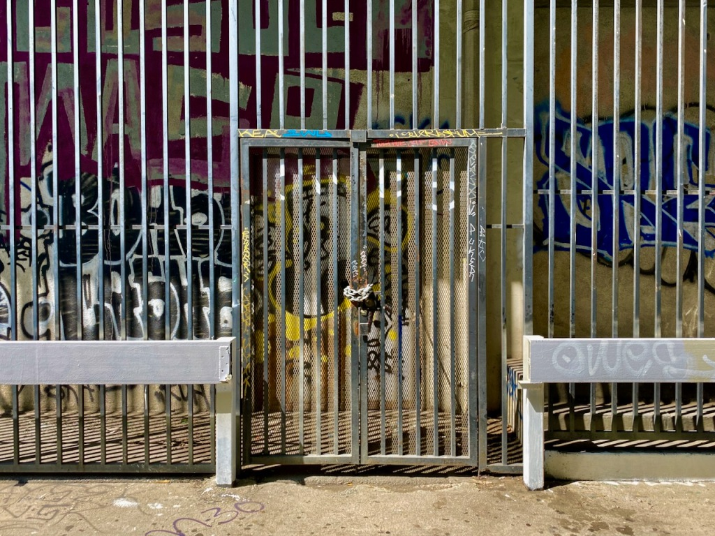 Street Photography: Graffiti Behind Bars and Chained Door